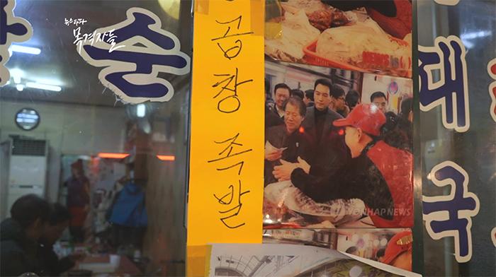 """▲ 중곡시장의 한 가게. 박근혜 대통령 방문 사진을 걸어 놨지만, 최근 손님들이 항의가 잇따르자, """"곱창, 족발 문구""""로 대통령의 얼굴을 가렸다."""