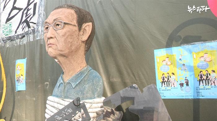 ▲ 연극인들이 광화문 광장에 설치한 블랙텐트 앞에 서 있는 김기춘 전 대통령 비서실장의 조형물
